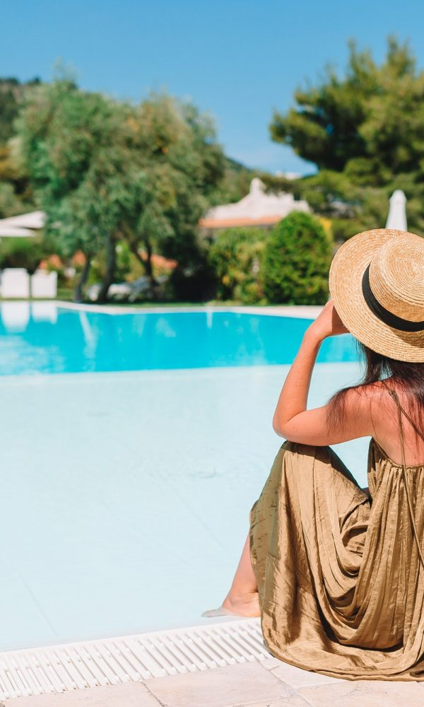 Blog Woman relaxing by the pool in a luxury hotel resort enjoying perfect beach holiday vacation