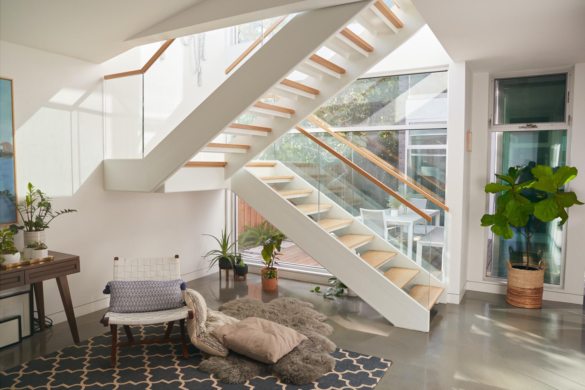 Reformas Casas Tenerife, vista interior de la hermosa sala de estar con escalera de vidrio y muebles suaves en la nueva casa familiar