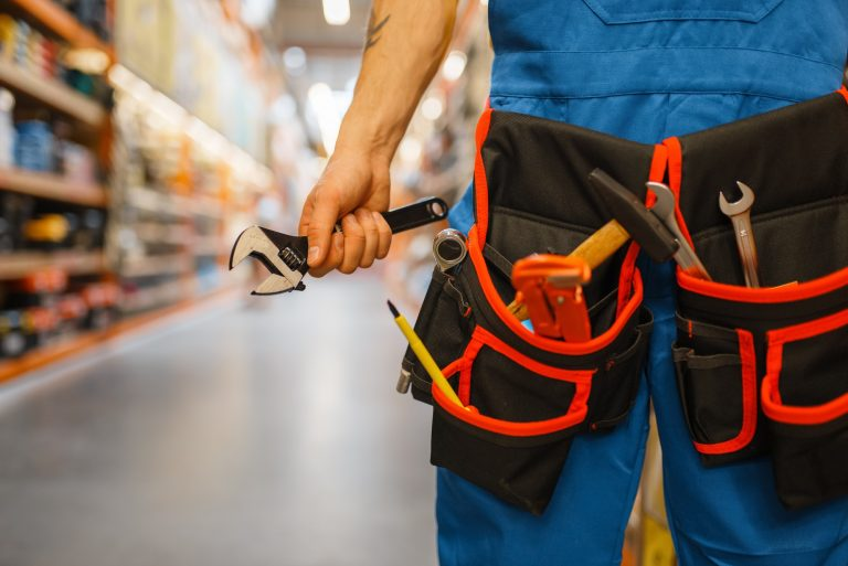 Male builder choosing tool belt in hardware store