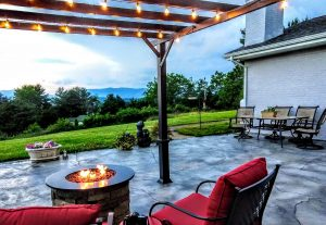 Outdoor living space with a fire pit, comfy chairs, a lighted trellis and flowers on a patio